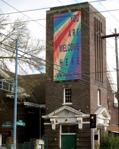 "exterior of the church with rainbow colored banner saying, ""you are welcome here"""